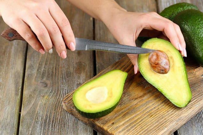 Плод авокадо разрезают пополам и извлекают косточку
